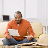 man on couch reading a pile of a4 papers
